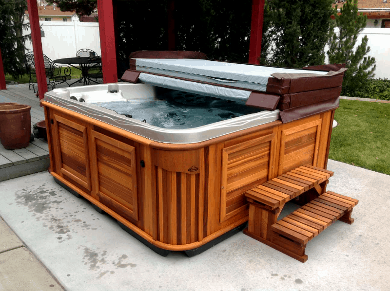 Half covered arctic spas hot tub in a backyard